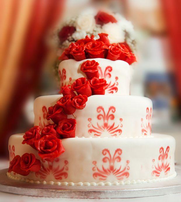Bolo branco com estampa em vermelho e flores de açúcar