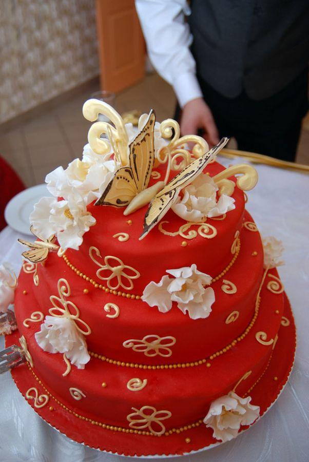 Bolo em vermelho e dourado, com confeitos em forma de borboletas