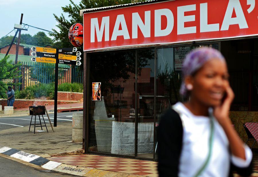 Moradora de Soweto passa por restaurante que leva o nome do ex-presidente sul-africano   / Carl de Souza/AFP