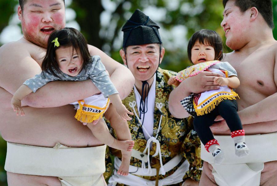 No evento, lutadores de sumô seguram bebês para começar a disputa
