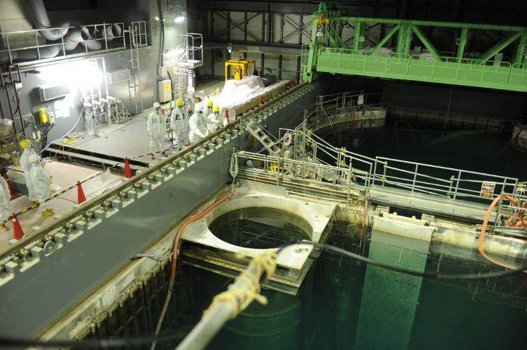 Técnicos observam a piscina do Reator 4 da usina nuclear de Fukushima / Tepco/AFP