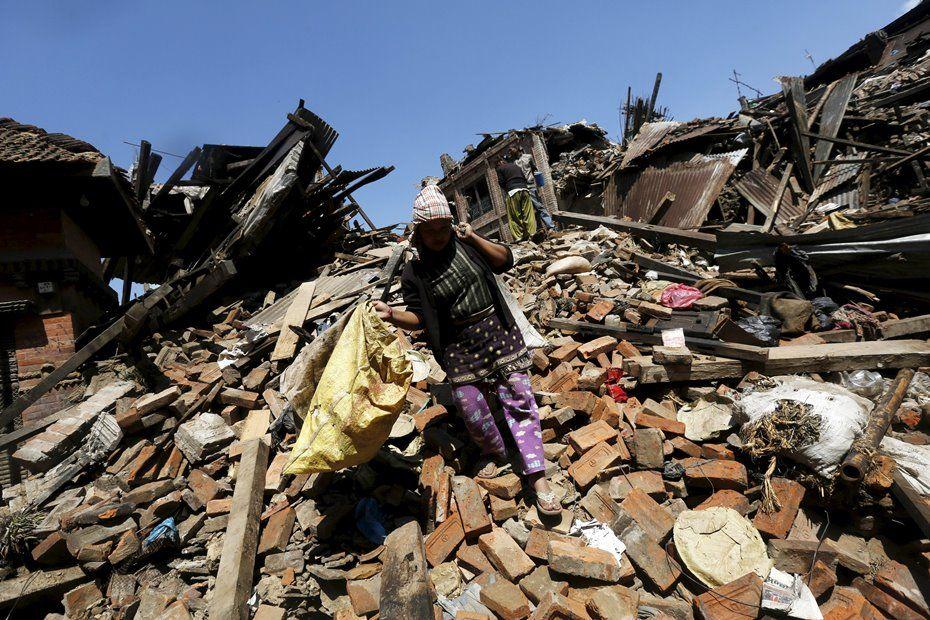 Mulher caminha sobre destroços de terremoto