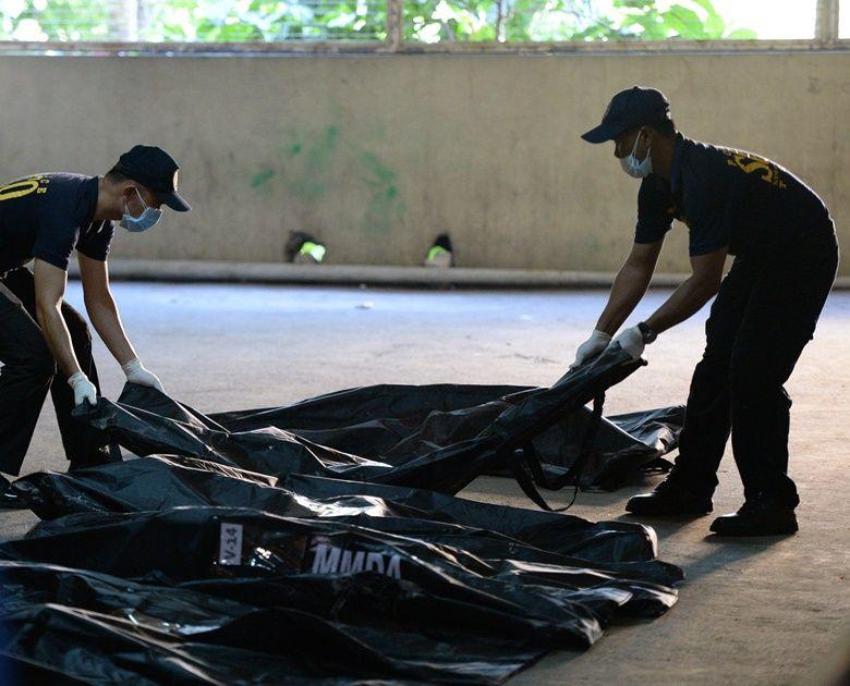 Policiais retiram corpos do local / TED ALJIBE / AFP