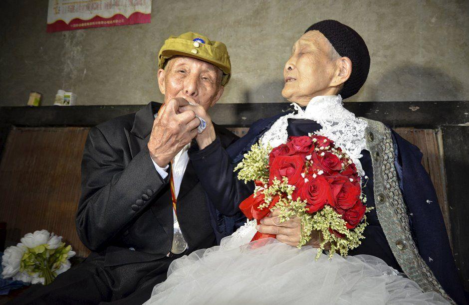 Yan beija a mão de sua esposa, Zhou / REUTERS/Stringer