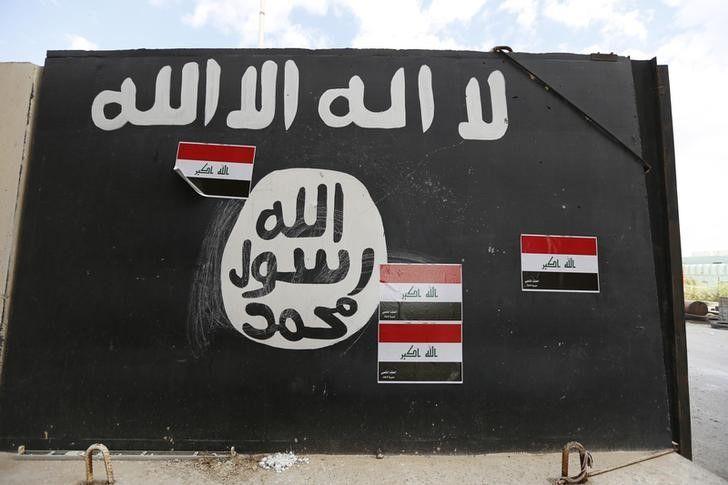 No Iraque, muro é pintado com bandeira normalmente usada por militantes do Estado Islâmico / Thaier Al-Sudani/Reuters