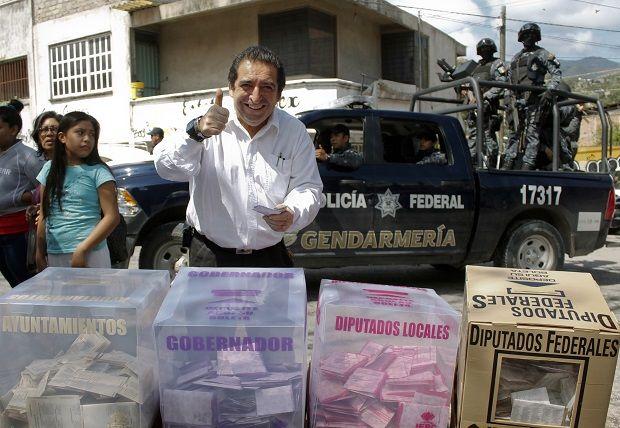 Eleitor mexicano acena enquanto a Polícia Federal patrulha as conturbadas eleições