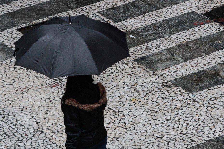 Pedestres se protegem da chuva na região do Viaduto do Chá / Leonardo Benassatto/Futura Press/Folhapress