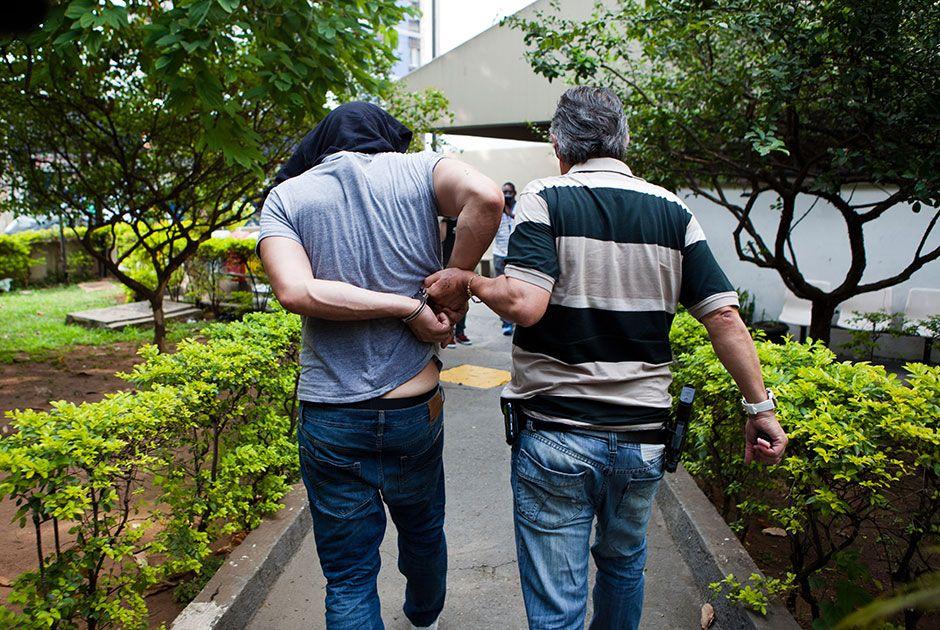 Magalhães (de blusa no rosto) sendo levado para fazer exame de corpo de delito, em 2013 / Bruno Poletti/folhapress, ILUSTRADA/Arquivo