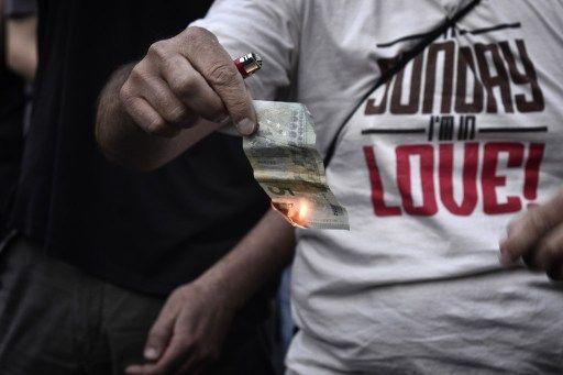 Manifestante queima nota de cinco euros em Atenas / AFP