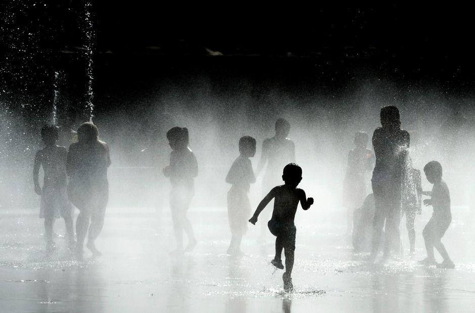Crianças se refrescam em fonte de água / DANI POZO / AFP