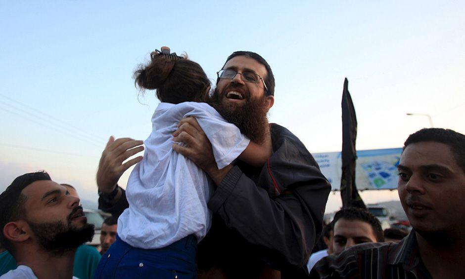 Adnane abraça a filha ao ser libertado / Reuters/Stringer
