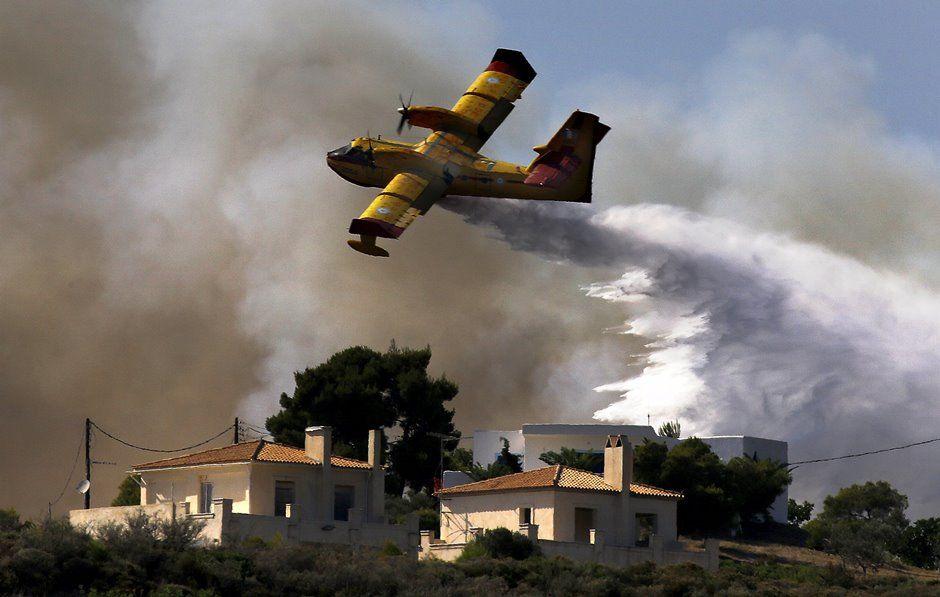 Avião combate incêndio na Vila Costa, Grécia / REUTERS/Yannis Behrakis