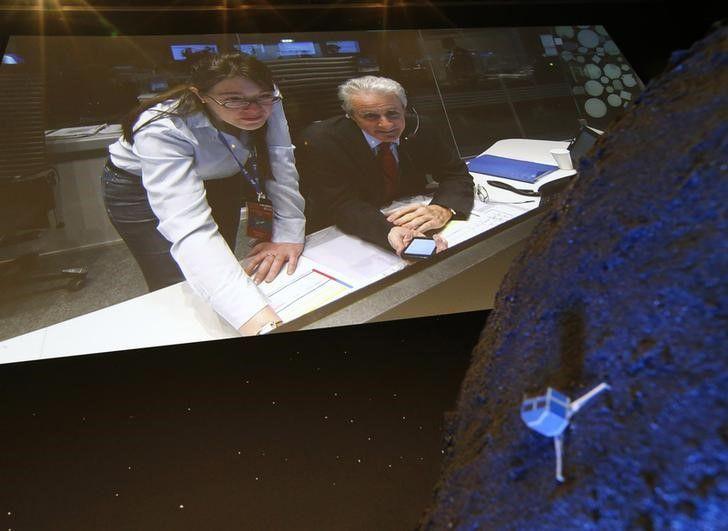 Pesquisadores em vídeo são vistos atrás da Philae estacionada em cometa / REUTERS/Ralph Orlowski
