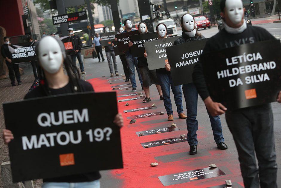 Manifestantes seguram placas com nome das vítimas de chacinas em Barueri e Osasco / Leonardo Benassatto/Futura Press/Folhapress