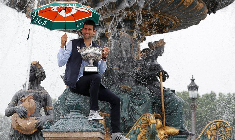 De guarda-chuva, Djokovic tira fotos com taça de RG