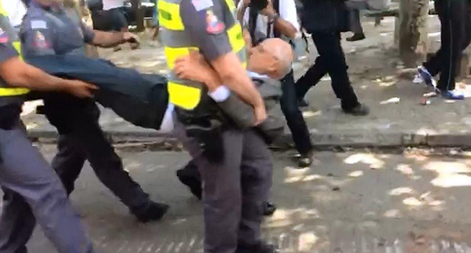 Ele foi carregado pelos braços e pernas por 4 policiais / Reprodução/Band