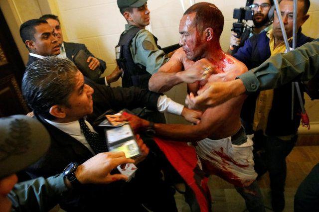 Manifestante ferido tenta sair de prédio da Assembleia Nacional da Venezuela  / Carlos Garcia Rawlins/Reuters
