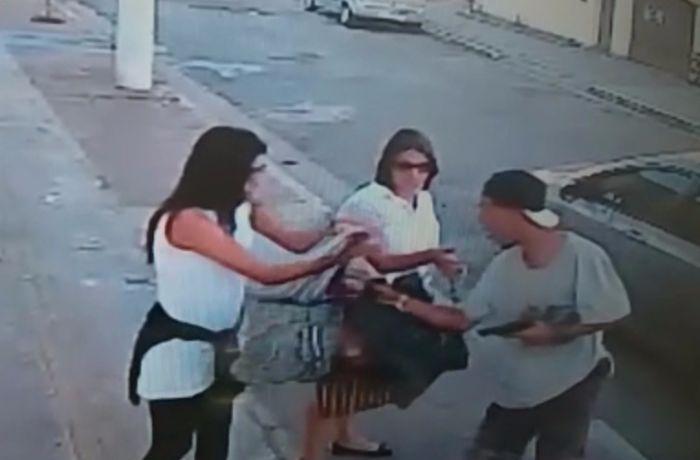 Um homem de boné sai de um carro para roubá-las. / (Foto: Reprodução)