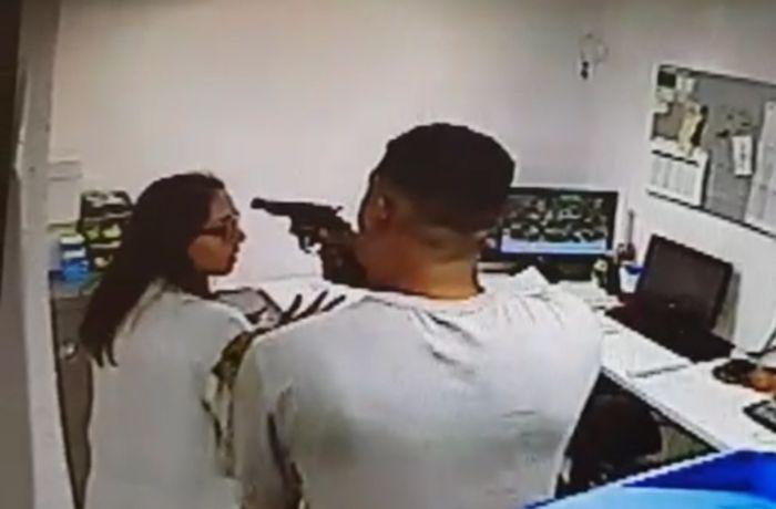 Um dos bandidos rende a funcionária da farmácia / (Foto: Reprodução Vídeo)