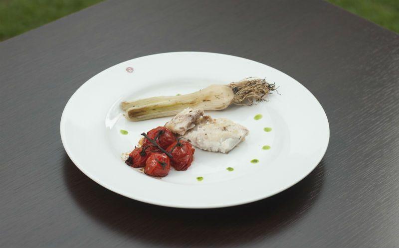 Pescada-cambucu na chapa ao molho de azeite e limão siciliano, tomate na brasa e alho-poró