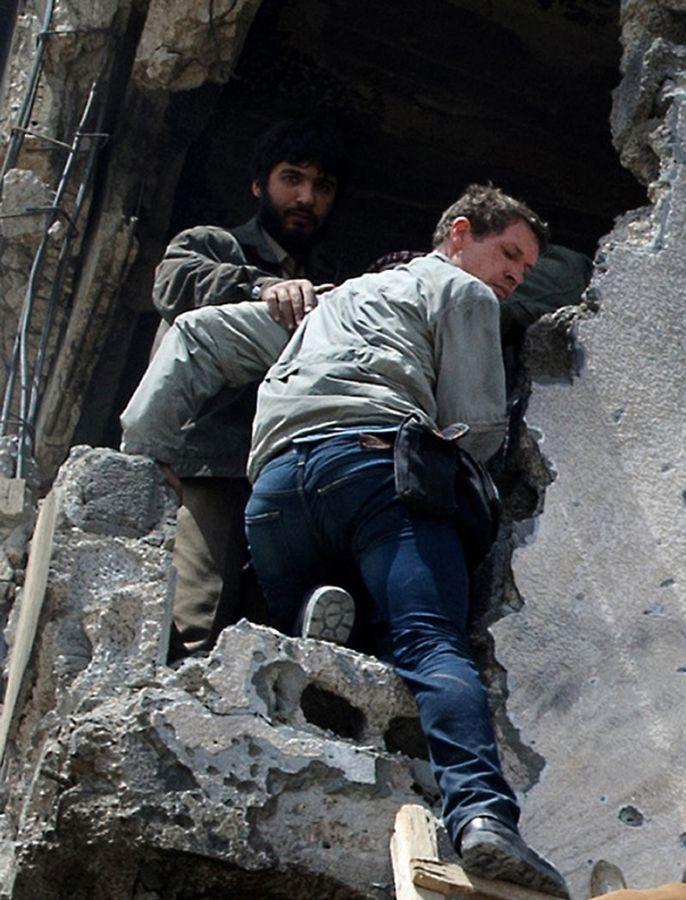 Foto mostra o jornalista Tim Hetherington recebendo ajuda de um rebelde líbio momentos antes de ser morto