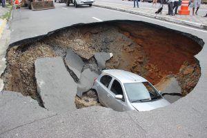 Um veículo que passava pelo local foi engolido pela cratera que se abriu na pista / Divulgação/ PMT