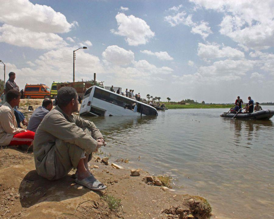 Egípcios olham para o mini-ônibus que afundou no Rio Nilo