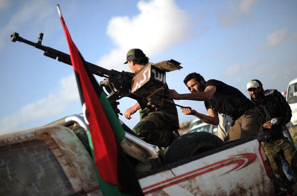 Homens recarregam uma metralhadora durante uma reunião dos rebeldes, na Líbia