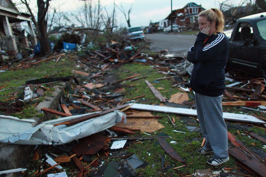 Moradora olha casa destruída em Joplin, onde um grande tornado matou ao menos 117 pessoas