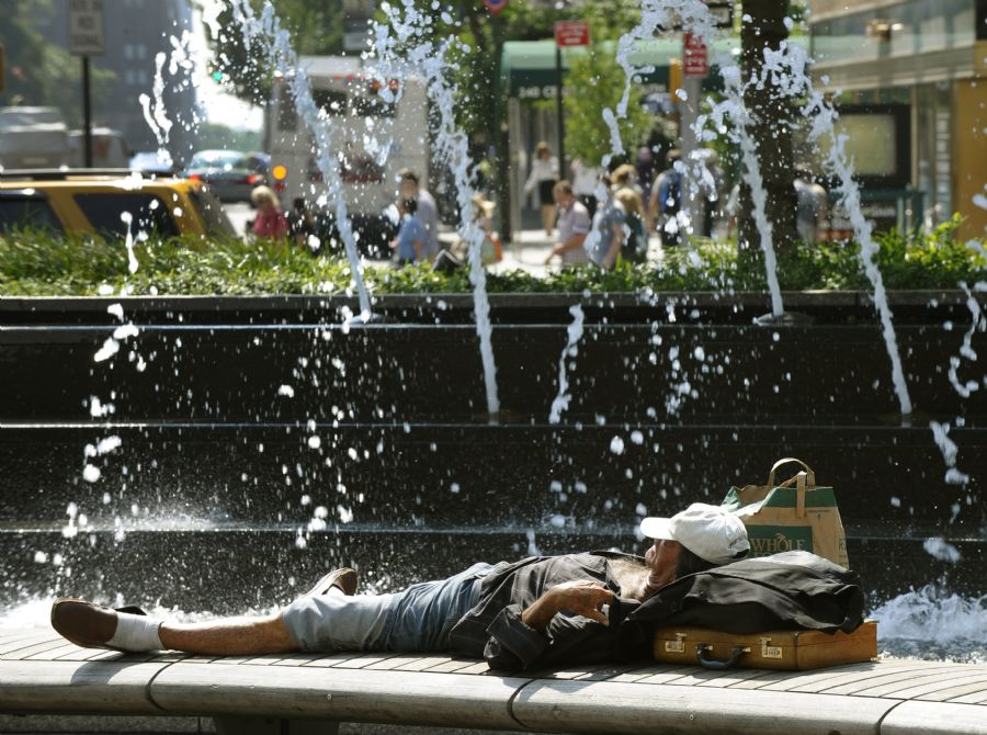Homem tenta se refrescar ao lado de fonte em Nova York, onde as temperaturas passam dos 30 graus / Timothy Clary/ AFP