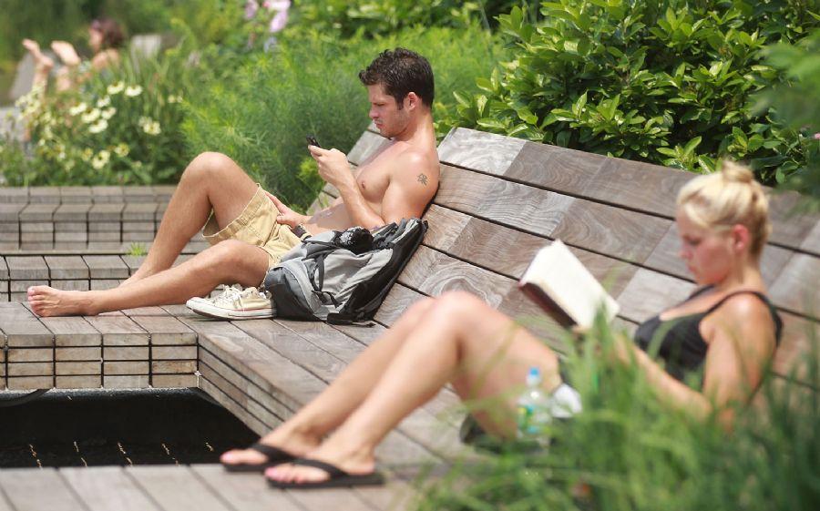 Pessoas lêem enquanto descansam no parque suspenso a nove metros de altura / Mario Tama/ Getty Images North America/AFP