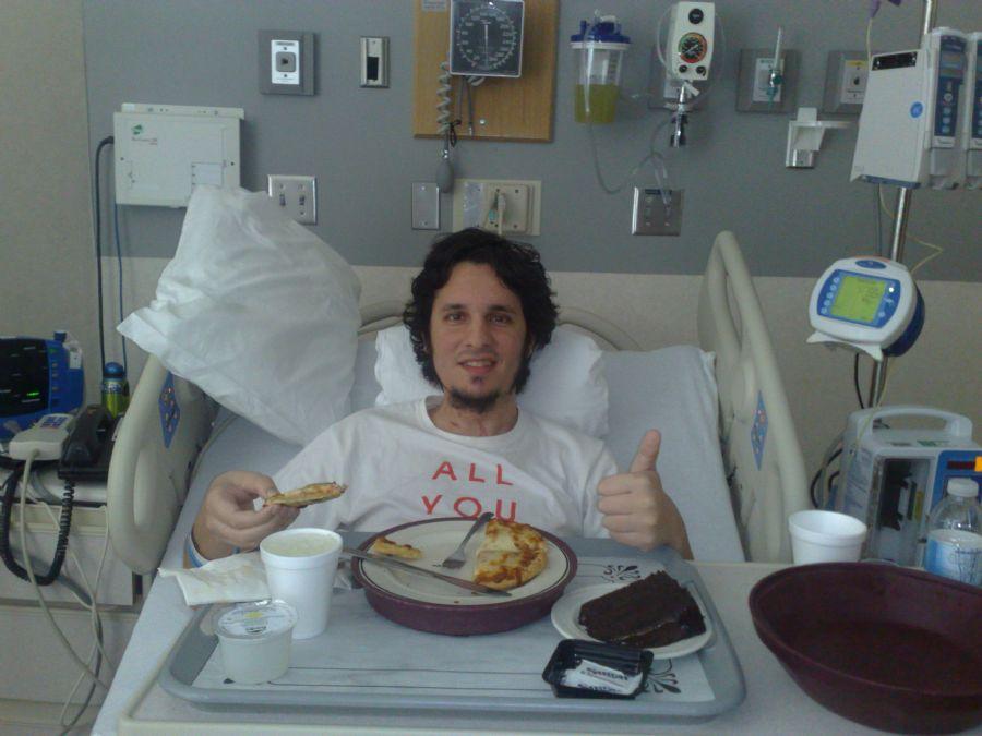 Renato, após o transplante, faz sua primeira refeição tipicamente norte-americana no hospital: pizza e bolo de chocolate / Arquivo Pessoal