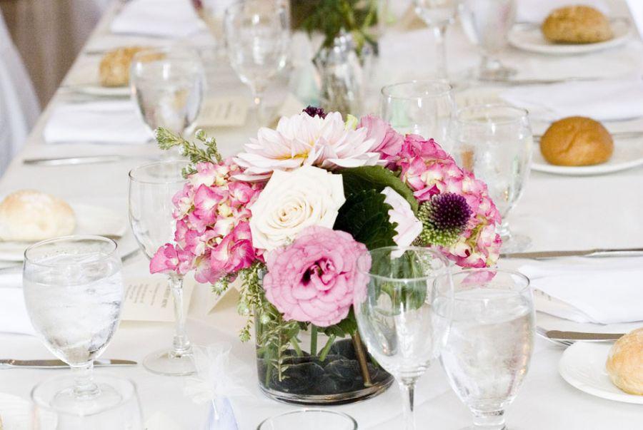 Um enfeite de mesa com flores rosa se destaca na decoração