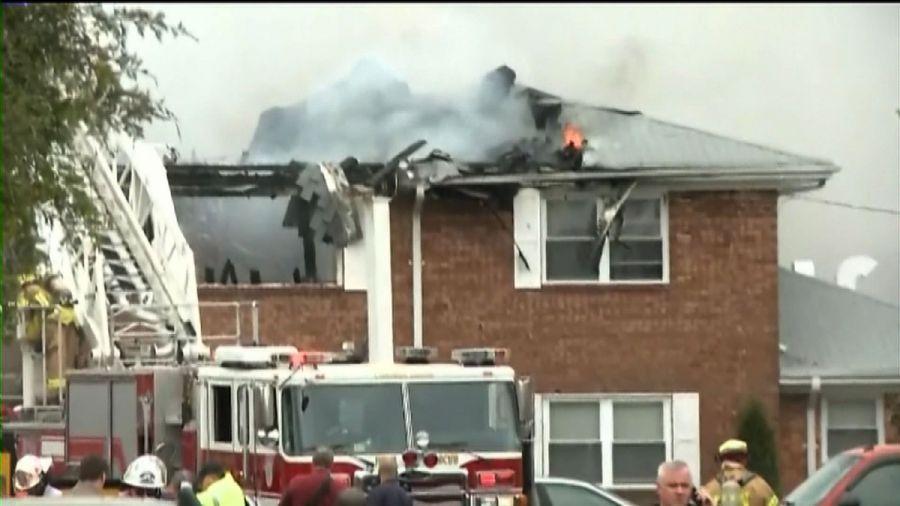 Bombeiros tentam conter o fogo  após um jato colidir com uma residência em Virginia Beach  / AFP/AFPTV/WKTR